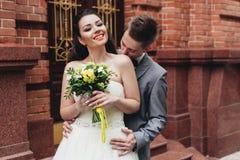 Groom kissing bride's shoulder. Young groom kissin his charming bride's shoulder Royalty Free Stock Image