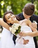 Groom kissing bride on shoulder . Groom kissing bride on shoulder outdoor Stock Images