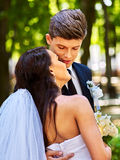 Groom kissing bride on shoulder Stock Image