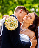 Groom kissing bride on shoulder. Groom kissing bride outdoor. Man gently embraces girl. Green background Royalty Free Stock Photography