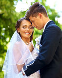 Groom kissing bride summer outdoor. Happy groom kissing bride summer outdoor Royalty Free Stock Photo
