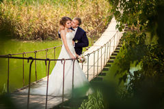 Groom kissing bride on suspension bridge Stock Photo
