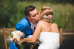 Groom Kissing Bride at Table. Groom kissing bride with bouquet at table Royalty Free Stock Photography