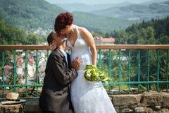 Groom kissing bride on their wedding day. Stock Photos
