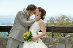 Groom kissing bride on their wedding day. Royalty Free Stock Photography