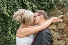 Groom kissing bride on their wedding day. Royalty Free Stock Photo