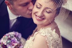 Groom kissing bride. On their wedding day Royalty Free Stock Images