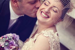 Groom kissing bride Stock Photography