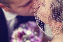 Groom kissing bride. On their wedding day Royalty Free Stock Photos