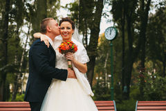 Groom kissing bride to cheek. In park Stock Photo