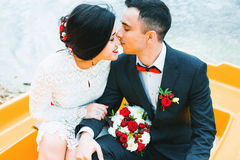 Groom kissing bride to nose in boat. On water Stock Images