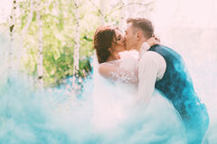 Groom kissing bride in turquoise smoke on nature. At sunny day Stock Photos