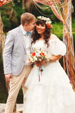 Groom kissing bride under arch Stock Photos