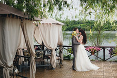 Groom kissing bride on the veranda. Elegant groom kissing his happy bride on the veranda Stock Images