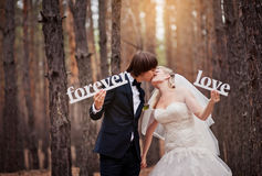 Groom kissing the bride at a wedding in the autumn forest and ho. Lding in their hands the letters forever love Stock Photo