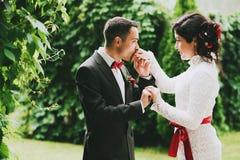 Groom kissing hand of bride in garden Stock Photo