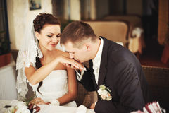 Groom kissing hand of his lovely bride stock image