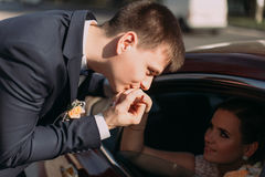 The groom is kissing the hand of the sitting in the car bride. Stock Photos