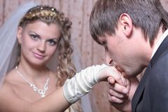 Groom kissing hand of smiling bride Stock Image
