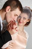 Groom kissing hand of smiling bride Stock Photos