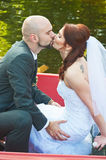 Groom kissing his bride. Groom giving new wife a kiss in the park after the religious ceremony Stock Image