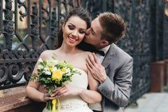 Groom kissing his bride. Handsome groom kissing his charming elegant bride Royalty Free Stock Photos
