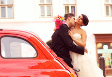Groom kissing his bride near a red car Stock Photos