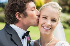 Groom kissing his pretty blonde wife on the cheek Royalty Free Stock Photography