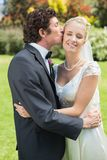 Groom kissing his pretty new wife on the cheek Royalty Free Stock Images