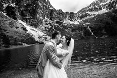 The groom kissing his young bride, on the shore of the lake Morskie Oko. Poland. Black and white photo stock photography