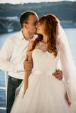 Groom kissing redhead bride at sunny day on riverbank Royalty Free Stock Images
