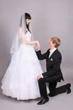 Groom kneels and holds bride hand in studio Stock Images