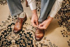 Groom laces brown shoes on a traditionally carpet on the wedding day. In the morning Stock Images