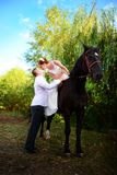 The groom leads the horse by the bridle. Bride sits in the saddl royalty free stock images