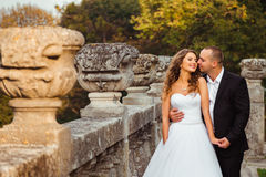 Groom leans to bride& x27;s cheek standing before old stone handrails.  Stock Photo