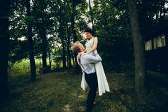 Groom lifted bride in his arms Stock Photo