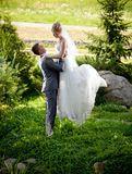Groom lifting up high beautiful bride at park Royalty Free Stock Images