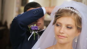 Groom lifts veil from face of bride stock video