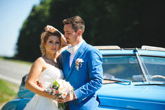 Groom Looking at Bride. At blue car Royalty Free Stock Images