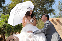 Groom looking bride with umbrella sitting on a metal wheel Stock Images