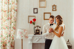 Groom looks with love at bride& x27;s hands royalty free stock photo