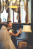 Groom looks proud dancing with bride in vintage hall Stock Photos