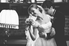 Groom looks proud dancing with bride in vintage hall Stock Image