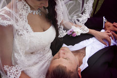 Groom lying on his bride`s hands Royalty Free Stock Photos