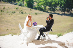 Groom Making Photo of Bride. At table Stock Photography