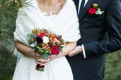 Groom with marsala boutonniere  and bride with red rose bouquet. Hold each other hands on wedding day Stock Photos