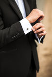 Groom in the morning buttoning cuffs on his suit Stock Photo