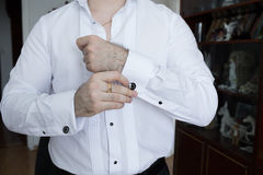 Groom in the morning wears a white shirt to wedding and adjusting cufflinks. Stock Photo