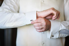 Groom in morning on wedding day buttoning cuffs his hands Stock Image