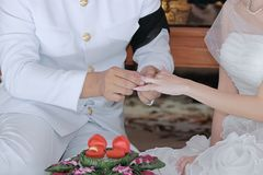 Groom newlyweds wearing ring on bride`s finger in wedding ceremony. Groom newlyweds wearing ring on bride`s finger in wedding ceremony Royalty Free Stock Photography